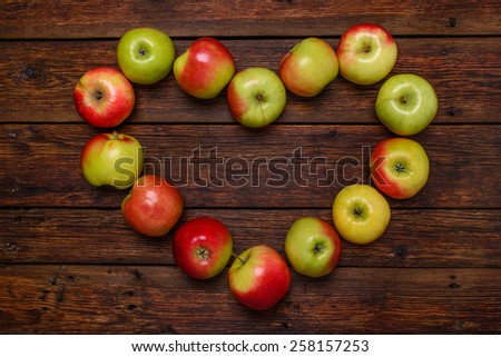 heart from fresh organic red apples on wooden table close-up - stock photo