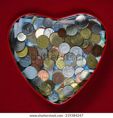 Heart from money coins  with red background - stock photo