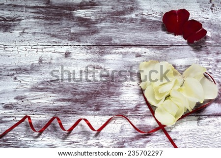 Heart from petals of red and white roses on Valentine`s Day on wooden background.Copy space. - stock photo