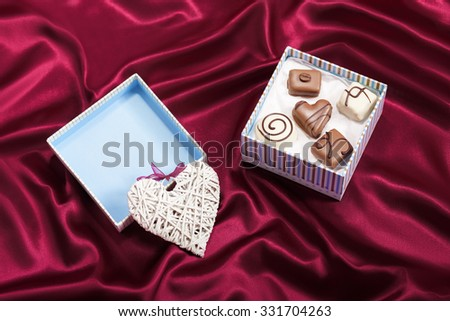 Heart gift decoration with chocolate candies in box on red satin background - stock photo