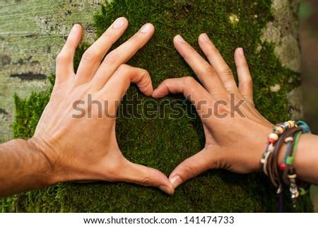 Heart hand on tree with moss by man and woman, loving the nature - stock photo
