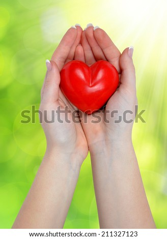 heart in hands on green natural background - stock photo