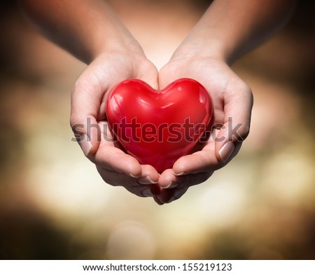 heart in heart hands- warm background - stock photo