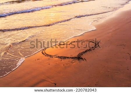 Heart in the sand on the beach with wave approaching  - stock photo