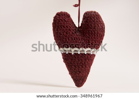 Heart knitted toys for Christmas tree, decorated with beads, lace and ribbons - stock photo