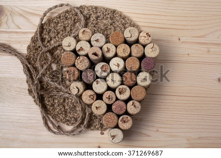 Heart laid out from bottle corks on wooden background - stock photo