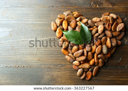 Heart made of aromatic cocoa beans on wooden background - stock photo