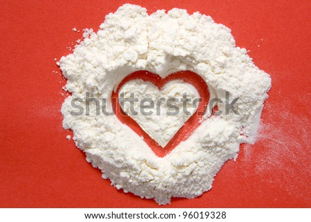 Heart made of flour. Isolated on red background - stock photo