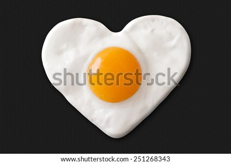 heart made of fried egg on teflon pan - stock photo