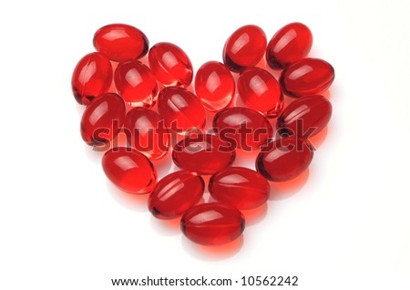 Heart made of red capsules on white background - stock photo