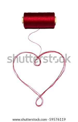 Heart made of red thread with spool. - stock photo