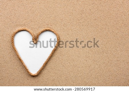 Heart made of rope with a white background on the sand, with place for your text - stock photo