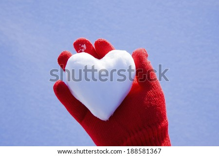 Heart made of Snow held by red glove  - stock photo
