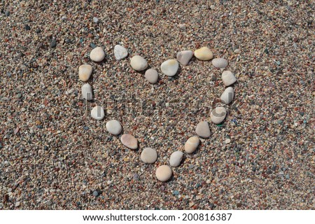 Heart made of stones on sand - stock photo
