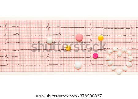 Heart made of white heart shape tablets and white, yellow and pink tablets on paper ECG results isolated on white background. Clipping path included. - stock photo