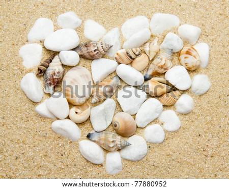 heart made with shells. Heart shape on sand - stock photo