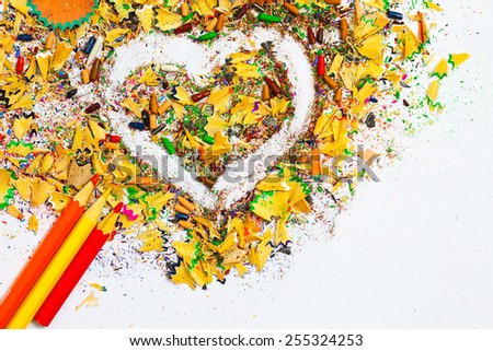 heart, multicolored pencils and varicolored wooden shavings on the white background - stock photo