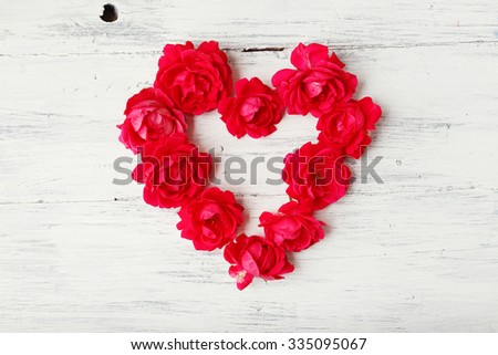 Heart of a red garden roses on white wooden background  - stock photo