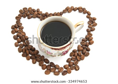 Heart of coffee beans and cup of coffee  - stock photo