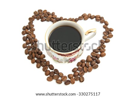 Heart of coffee beans and cup of coffee on white - stock photo
