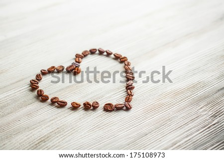 Heart of coffee beans on a white board - stock photo