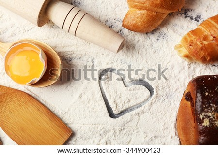 Heart of flour, croissant and  wooden kitchen utensils on gray background - stock photo