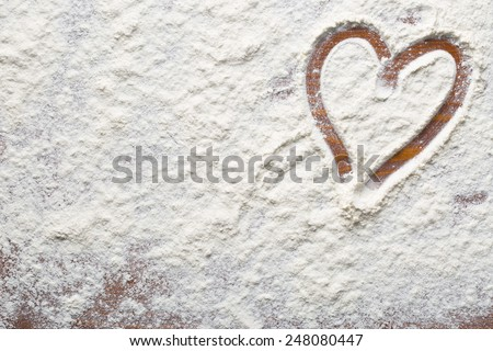 heart of flour on wooden table - stock photo