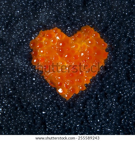 Heart of red caviar on a background of black caviar - stock photo