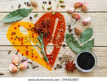Heart of spices and seasonings. Turmeric, paprika, cumin, rosemary, garlic, cardamom, nutmeg, clove Bud, Bay leaf, star anise, green and pink pepper, juniper, coriander, Nigella - stock photo