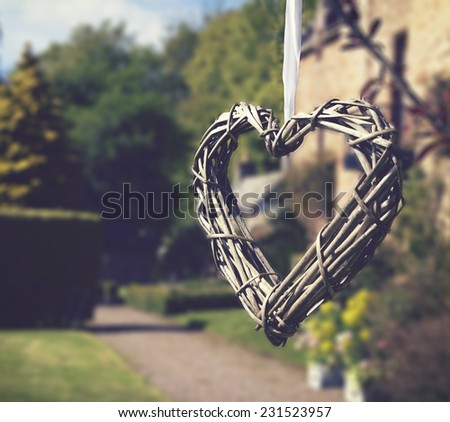 Heart of sticks hanging in beautiful wedding gardens - stock photo