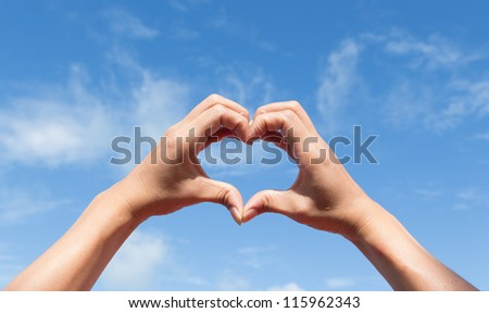 heart of the fingers against the blue sky - stock photo