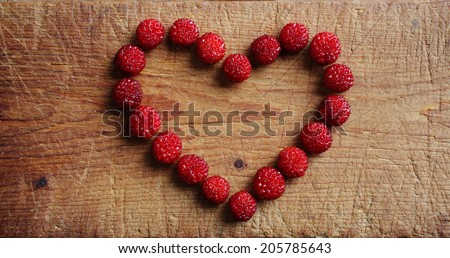 Heart of wild strawberries at wooden cutting board. Closeup, daylight.  - stock photo
