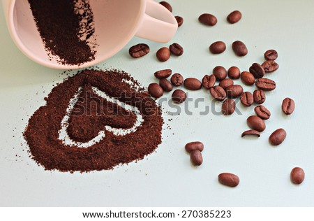 heart on coffee grounds and beans scattered from cup  - stock photo