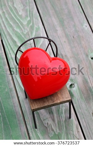 heart on small toy chair, grunge wood background - stock photo