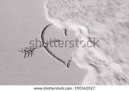 Heart on the beach getting wash out. Broken heart. - stock photo