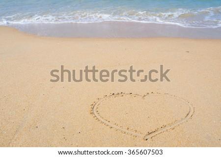 heart outline on the wet beach sand against sea wave - stock photo
