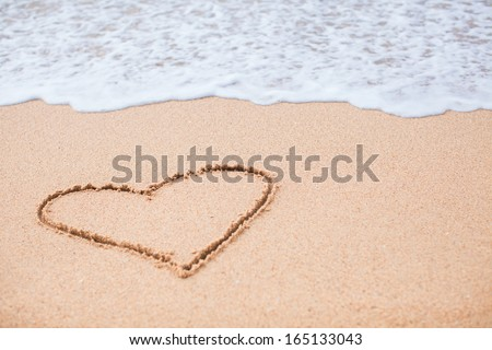 Heart painted in the sand on a tropical beach - stock photo