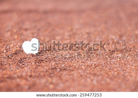 heart paper standing on cocoa powder - stock photo