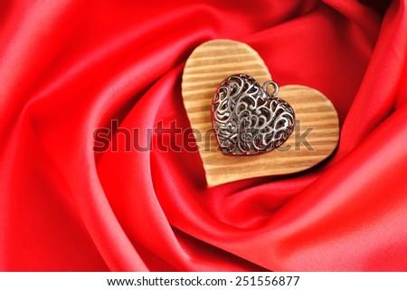 Heart pendant on satin fabric background - stock photo