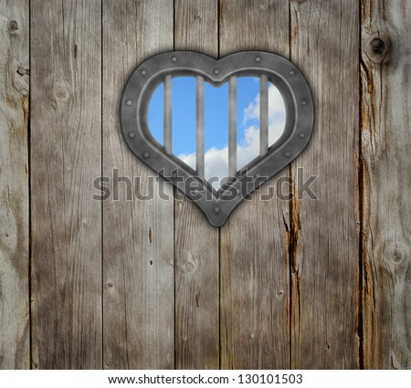 heart prison window on wooden planks background - stock photo
