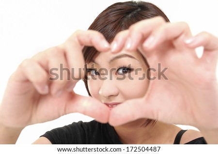 Heart shape. Beautiful young woman holding her hands in heart shape and smiling at camera - stock photo