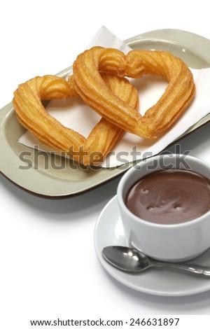 heart shape churros and hot chocolate on white background - stock photo