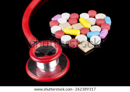 Heart shape Colored pills medicine  on black background with red stethoscope - stock photo