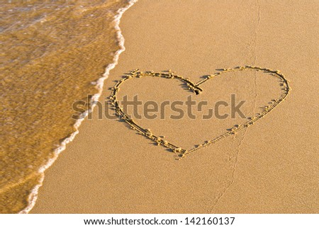 Heart shape drawing in the sand - stock photo