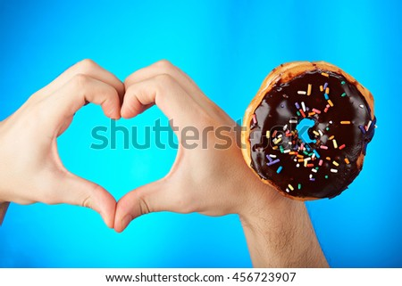 Heart shape from hands for donuts isolated on blue - stock photo