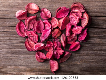 Heart shape made from potpourri on wooden table - stock photo