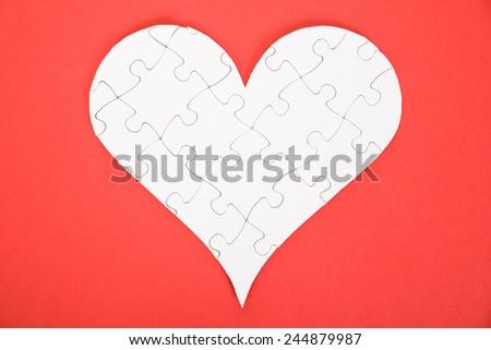 Heart Shape Made Of White Jigsaw Puzzle Over Orange Background - stock photo