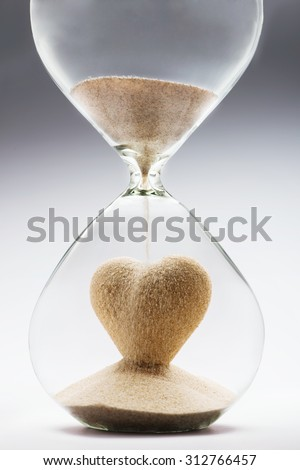 Heart shape made out of falling sand inside hourglass - stock photo