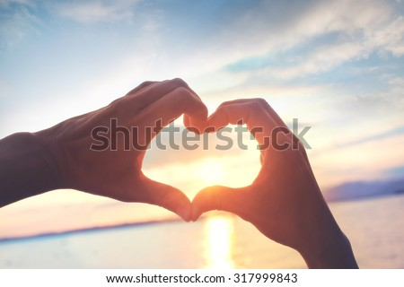 Heart shape made with hands at sunset - stock photo