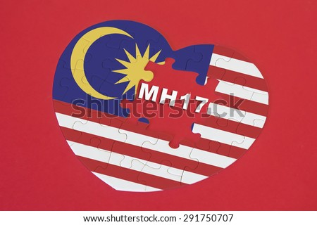 Heart shape Malaysia Flag jigsaw puzzle with a written word MH17 with red background. Malaysia Airlines flight MH17 was shot down on 17 July 2014. - stock photo